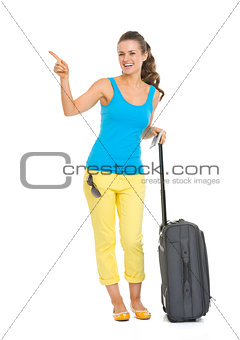 Smiling young tourist woman with wheel bag pointing on copy spac