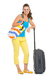 Smiling young tourist woman with wheel bag