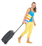Smiling young tourist woman with wheel bag going sideways