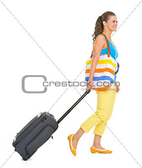 Young tourist woman with wheel bag going sideways
