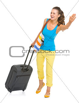 Smiling young tourist woman with wheel bag catching taxi