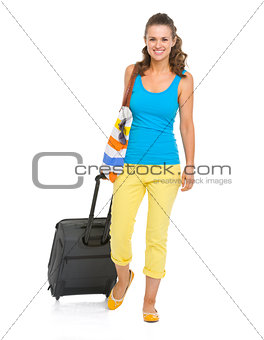 Smiling young tourist woman with wheel bag going straight