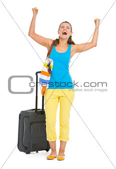 Happy young tourist woman with wheel bag rejoicing