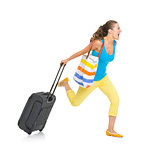 Concerned young tourist woman with wheel bag rushing