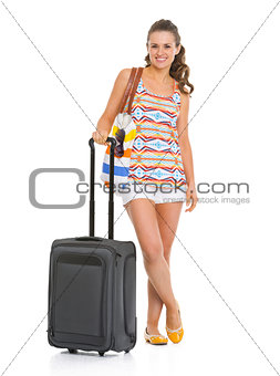 Full length portrait of smiling young woman with wheel bag going