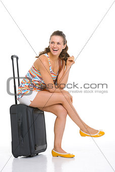 Smiling young tourist woman sitting on wheel bag and looking on