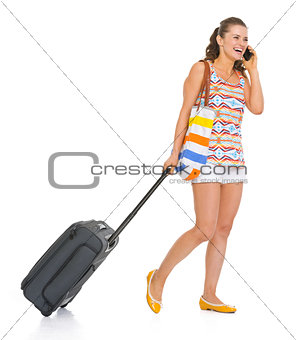 Happy young tourist woman with wheel bag walking and talking mob