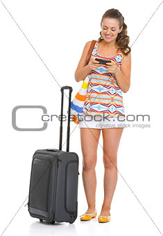 Happy young tourist woman with wheel bag writing sms