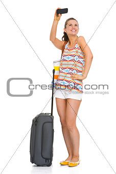 Happy young tourist woman with wheel bag taking self photo