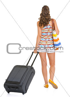 Young tourist woman with wheel bag going straight . rear view