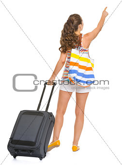 Young tourist woman with wheel bag pointing on copy space . rear