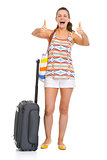 Happy young tourist woman with wheel bag showing thumbs up