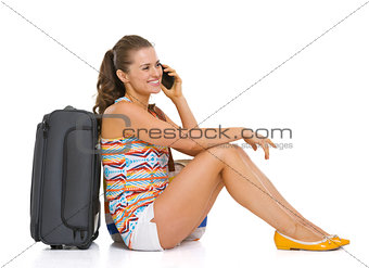 Happy young tourist woman sitting near wheel bag and talking cel