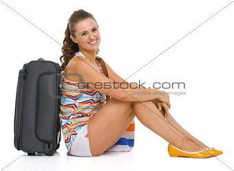 Smiling young tourist woman sitting near wheel bag