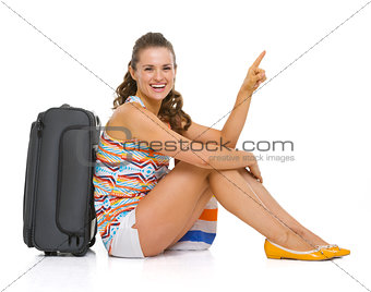 Happy young tourist woman sitting near wheel bag and pointing on