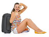 Smiling young tourist woman sitting near wheel bag and framing w