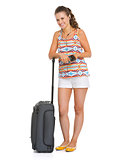 Smiling young tourist woman with wheel bag listening music
