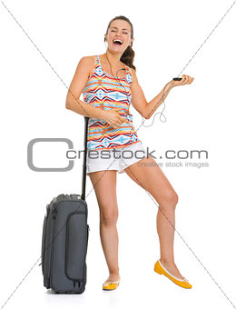 Smiling young tourist woman with wheel bag listening music and d