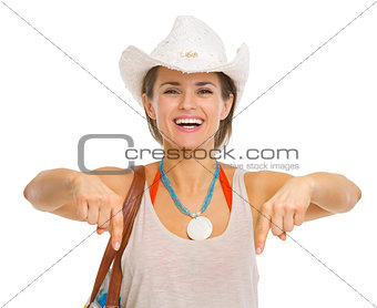 Smiling young beach woman in hat pointing down on copy space