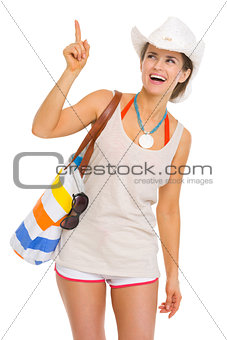 Smiling young beach woman in hat pointing on copy space