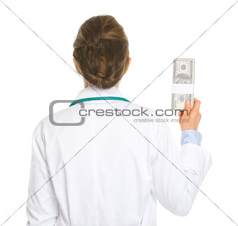 Medical doctor woman holding pack of dollars . rear view