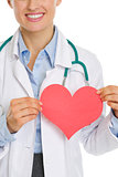 Closeup on medical doctor woman holding paper heart