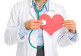 Closeup on medical doctor woman listening paper heart
