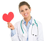 Smiling medical doctor woman holding paper heart