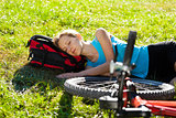Young cyclist enjoying sleeps relax lying in the fresh grass