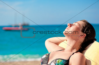 Portrait of sunbathing girl on a background of the sea and the schooner.