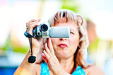 Woman shoots video with interest to the mini camcorder