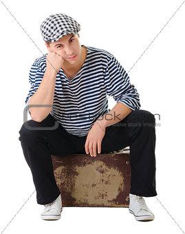Sad waiting young male traveler on vintage suitcase