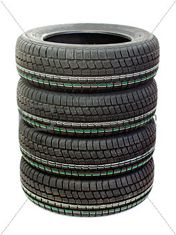 Four new tires stacked on white background
