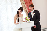 bride and groom signing a wedding document