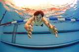 man in swimming pool streching hands