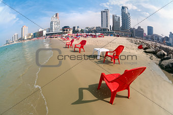 Red chairs on the sandy beach.