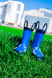 dark blue child rubber boots on a grass in a spring day