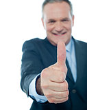 Smiling matured businessman showing thumbs-up