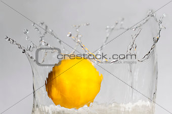 Lemon splashing into clear water on white background.