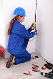 Female electrician checking socket