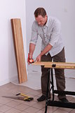 handyman measuring a wooden board with a measure-tape