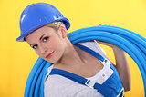 Blond plumber carrying plastic piping