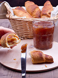 Hand with croisant and knife with jam