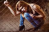 Beautiful young girl sitting behind metallic lattice