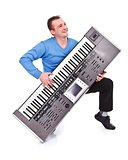 Happy man playing on synthesizer