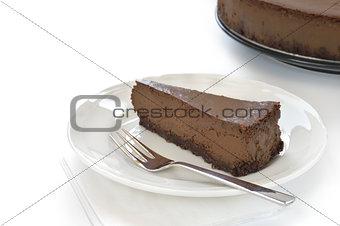 Slice of chocolate cheesecake on white plate