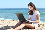 Beautiful woman with a laptop on the beach