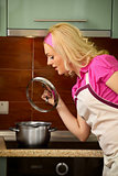 Blonde girl prepares food on kitchen