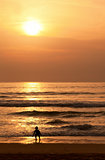 Child plays on the evening beach