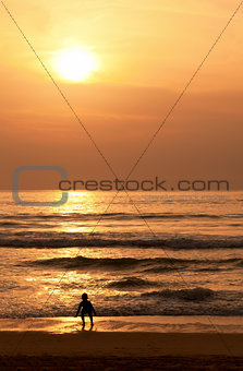 Child plays on the evening beach